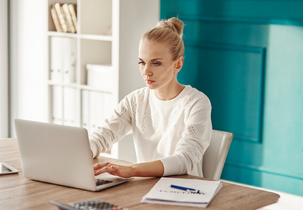 Serious businesswoman using laptop at office