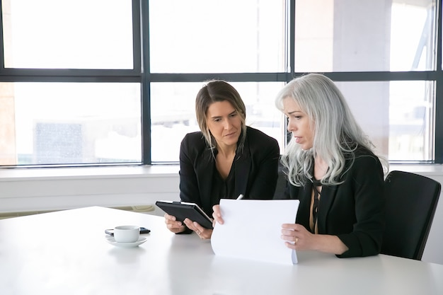 Serious businesswomen discussing reports. two female professionals sitting together, holding documents, using tablet and talking. communication concept