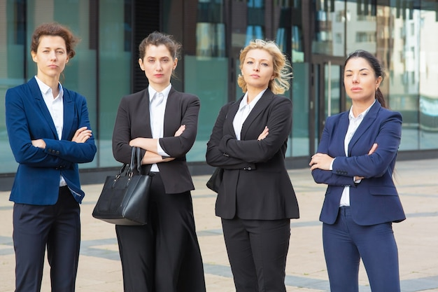 Serious businesswomen group with arms folded standing together near office building, posing, looking at camera. front view. business team or teamwork concept