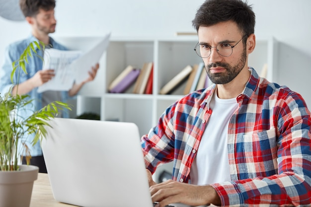 Serious bussinessman with thick beard, analyzes income charts and graphs on laptop computer, dressed in checkered shirt