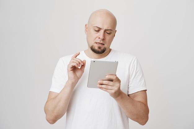 Ragazzo calvo occupato serio guarda la tavoletta digitale