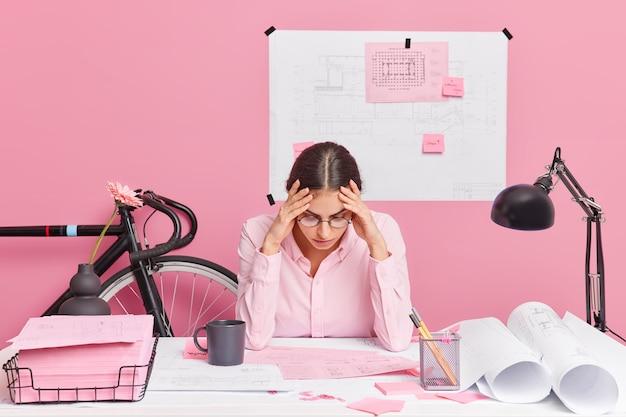 Серьезно занятая женщина-архитектор вносит коррективы в эскизы, старается сделать лучший вариант, поглощенная рабочим процессом, смотрит на технические планы целенаправленно. концепция работы профессии людей