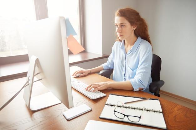 Impiegato di ufficio femminile occupato serio, tastiera sul computer