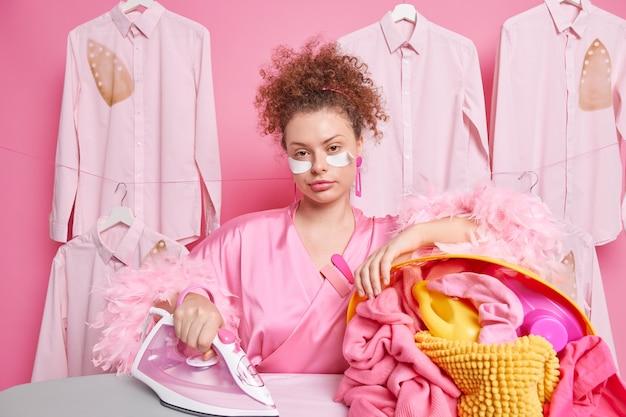 빗질 한 곱슬 머리를 가진 진지한 바쁜 주부는 그녀의 외모를 걱정하고 눈 아래에 패치를 적용합니다. 가정 가운을 입은 세탁 세탁물을 다림질하기 위해 전기 다리미를 사용합니다.