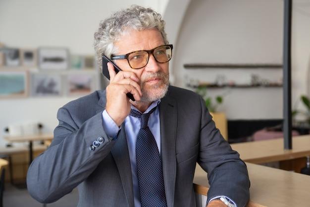 Grave imprenditore maturo impegnato con gli occhiali, parlando al telefono cellulare, in piedi al co-working, appoggiato sulla scrivania, guardando lontano