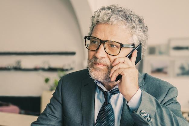 眼鏡をかけて、机の上の携帯電話で話している深刻な忙しい成熟したビジネスマン