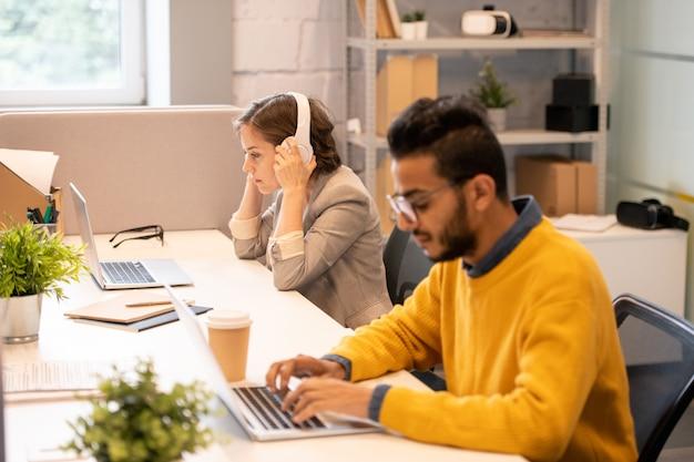 1つのテーブルに座ってオフィスでファイルを操作しながら最新のラップトップを使用している多忙な多民族マネージャー