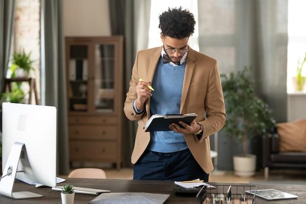 재킷과 스웨터를 입은 진지하고 바쁜 젊은 흑인 마케팅 매니저는 나무 테이블에 서서 홈 오피스에서 서류 작업을 합니다.