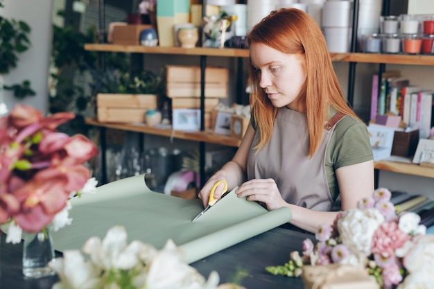 Serious busy young redhead woman in apron standing by counter and cutting wrap paper for flower packaging in flower store