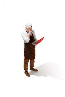 Serious butcher posing with a laptop isolated
