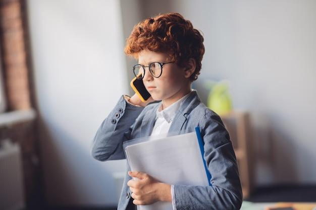 Серьезный звонок. рыжий мальчик в костюме разговаривает по телефону и выглядит серьезно