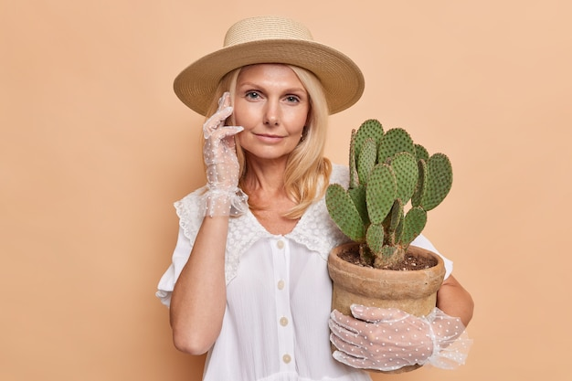 Serious calm blonde european woman looks directly at front wears fashionable outfit holds potted cactus takes care of houseplant isolated over brown wall