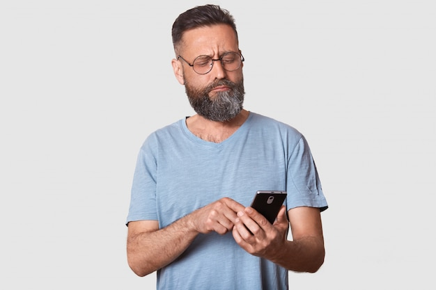 Serious calm brunette guy looks attentively aside, holding smart phone in his hand, typing messages to his friends, confused about posting. handsome model wearing casual t shirt and fashionable specs.