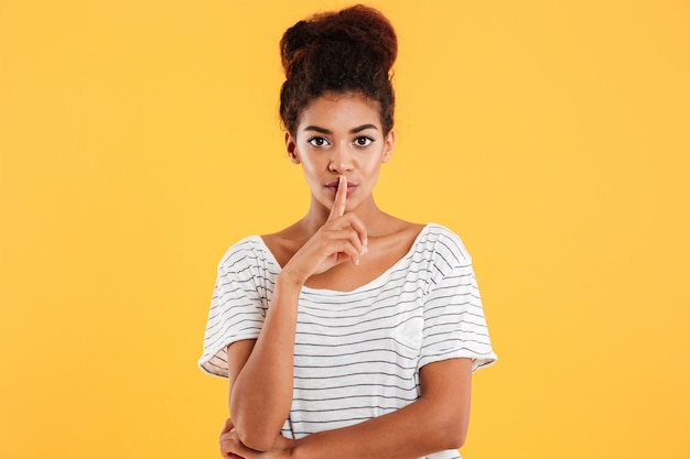 Serious calm confident woman showing silence gesture