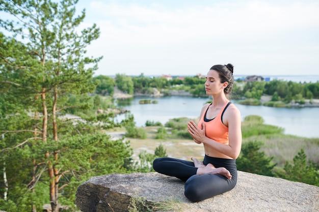 湖の石の蓮華座に座っていると瞑想しながらナマステジェスチャーを作る深刻な穏やかな若い女の子