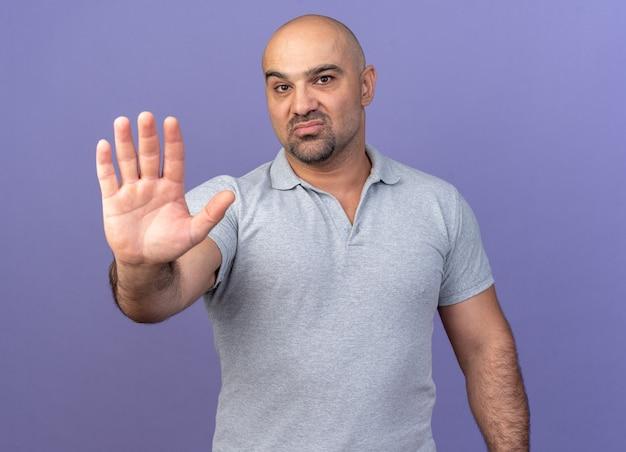 Серьезный случайный мужчина средних лет делает стоп-жест изолирован на фиолетовой стене
