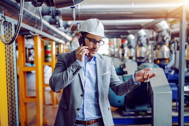 Serious caucasian businessman in with helmet on head having phone call while standing in power plant.