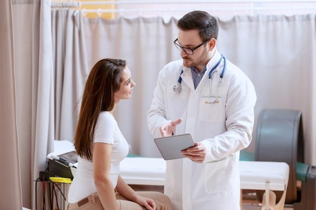 眼鏡とタブレットで彼の女性患者の治療計画を示す青い制服を着た深刻な白人医師。病院のインテリア。