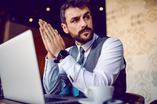 深刻な白人のエレガントなひげを生やした実業家スーツにカフェに座って、問題を解決する方法を考えています。テーブルの上の彼の前にはラップトップがあります。