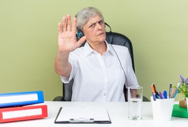 Operatore di call center femminile caucasico serio sulle cuffie seduto alla scrivania con strumenti da ufficio che gesturing il segno della mano di arresto isolato sulla parete verde
