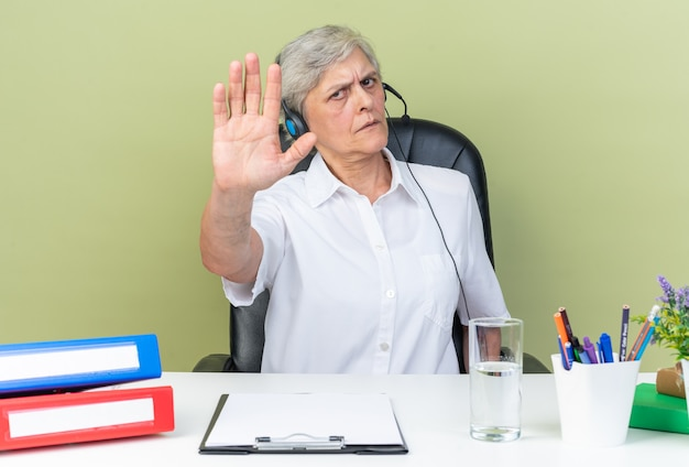 緑の壁に分離された一時停止の手札を身振りで示すオフィスツールと机に座っているヘッドフォンで深刻な白人女性のコールセンターのオペレーター
