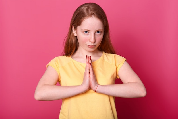 Серьезные кавказские девушки позируют с уверенным выражением, держит руки в молитве жест, носить желтую футболку, изолированных на розовый.