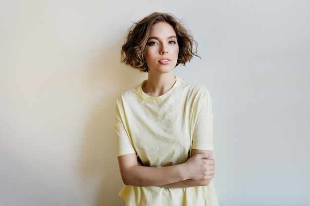 아늑한 티셔츠 포즈 팔에 심각한 백인 여자를 넘어. 흰 벽에 고립 된 매력적인 곱슬 젊은 아가씨의 실내 초상화.