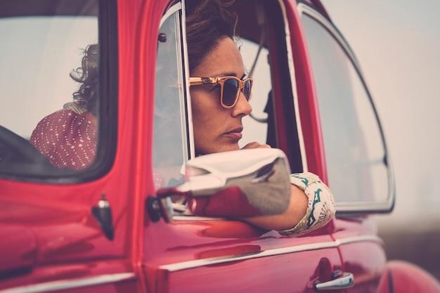 Серьезная кавказская дама смотрит на свою машину с мыслями