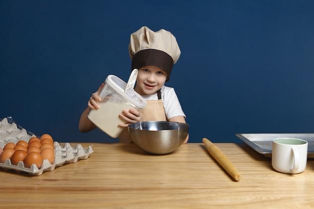 Bambino maschio caucasico serio che sorride mentre versa un po 'di farina nella ciotola del metallo