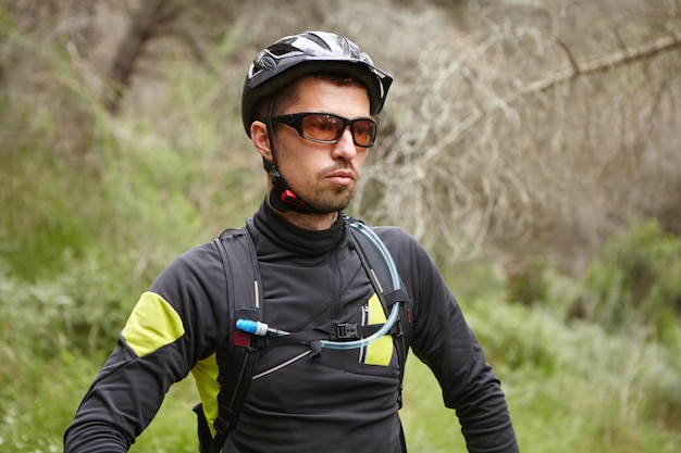 Serious caucasian male cyclist wearing protective helmet and glasses feeling tired after intensive cycling workout outdoors in forest on his booster bike
