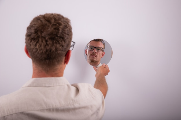 Serious caucasian man looks at himself in the mirror and reflects on life. pensive person with eyeglasses. guy isolated on white background, studio photo.