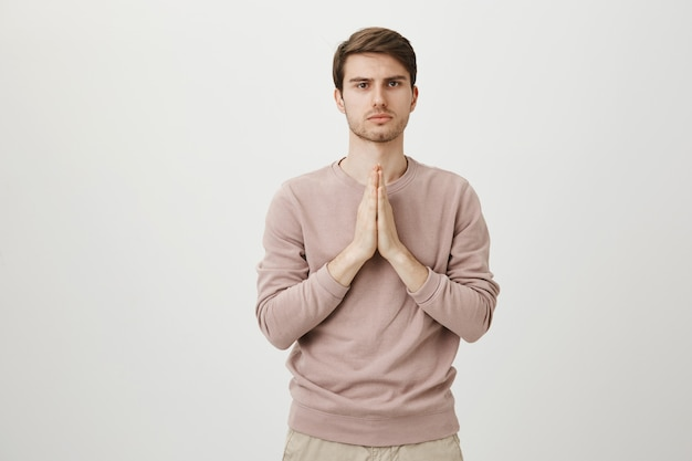 Serious caucasian man pleading, holding hands in pray as supplicating