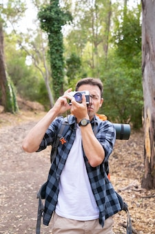 Serious caucasian man shooting landscape and hiking in forest. male traveler walking on nature, taking photo and standing on road. tourism, adventure and summer vacation concept