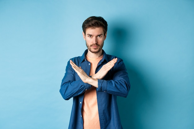 Serious caucasian man tell no, showing cross stop gesture and looking confident at camera, prohibit something bad, standing on blue background.
