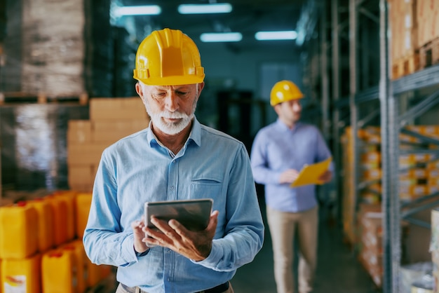 공식적인 마모 및 상품 확인을 위해 태블릿을 사용하여 머리에 보호용 노란색 헬멧에 심각한 백인 수석 성인 감사
