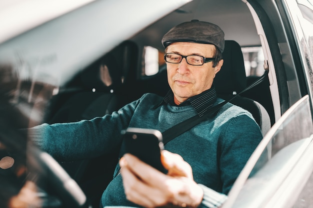 Serious caucasian senior man with cap on head and eyeglasses sitting in car and using smart phone