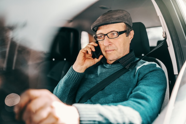 Serious caucasian senior man with cap on head and eyeglasses sitting in car with hand on steering wheel and using smart phone