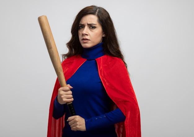 Ragazza seria del supereroe caucasico con mantello rosso che tiene la mazza da baseball isolata sulla parete bianca con lo spazio della copia