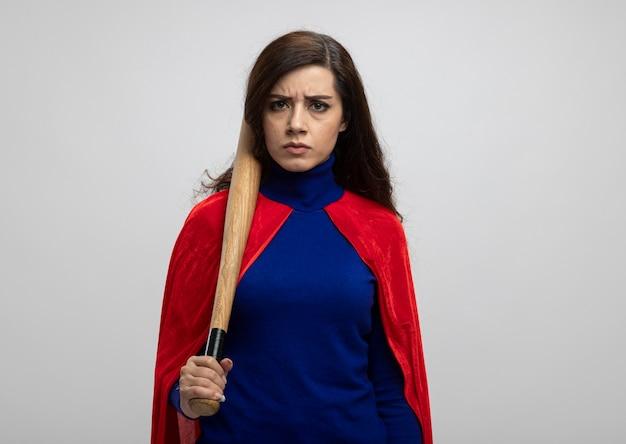 La ragazza caucasica seria del supereroe con il mantello rosso tiene la mazza da baseball isolata sulla parete bianca con lo spazio della copia