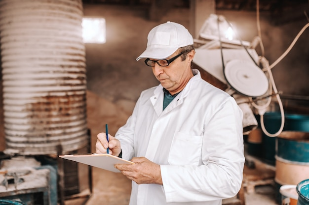 Serious caucasian veterinarian in white uniform writing down results of animal examination while standing in front of barn.