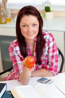 Serious caucasian woman holding an apple sitting in the kitchen