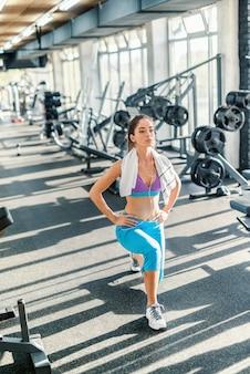 Серьезная кавказская женщина в спортивной одежде и полотенце на шее делает упражнения для ног. интерьер спортзала.