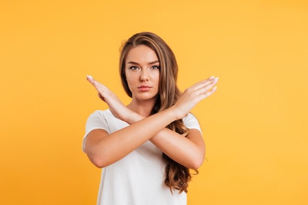 Serious caucasian woman standing near copyspace showing stop gesture.