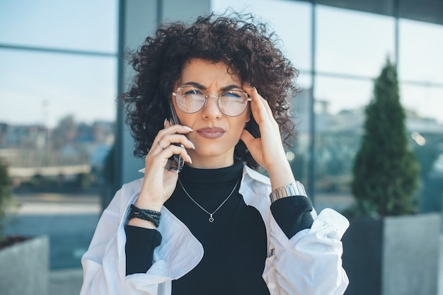 Serious caucasian woman with curly hair and glasses looking at camera while having a business phone discussion outside
