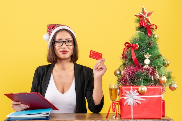 黄色の孤立したオフィスで銀行カードを示すサンタクロースの帽子と眼鏡とスーツの真面目な魅力的な女性