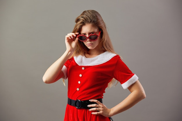 Serious charming mrs.santa claus in sunglasses dressed in the red robe and white gloves stands on the gray background. .