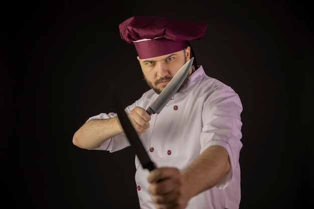 Serious chef man in uniform holds two knives crossing them as fighting