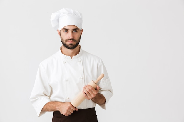 Serious chief man in cook uniform holding kitchen wooden rolling pin isolated over white wall