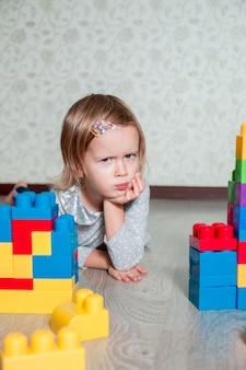 明るいプラスチック製の建設ブロックの近くに横たわっている深刻な子供の女の子。床で遊ぶ幼児。おもちゃの開発。初期の学習。