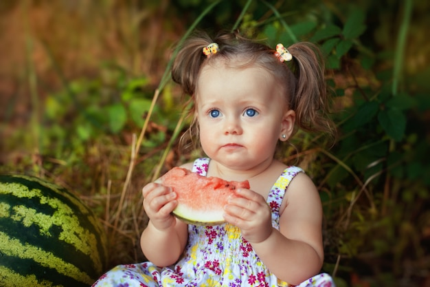 Serious child with juicy watermelon.